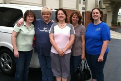 5 moms on a conference trip posing by their van