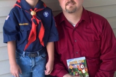 Dad posing with young Cub Scout son in uniform