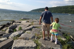 dad helps daughter with leg braces over rocks by lake