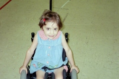 toddler girl in tiny wheelchair