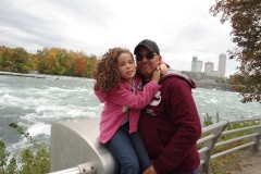 young girl hugging dad in front of Niagara Falls