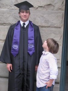 Little brother looks up at big brother on graduation night