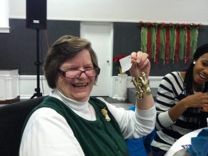 Joyce Herzog laughing while holding up Christmas ornament at event