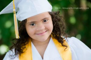 child with Down Syndrome dressed to graduate from kindergarten