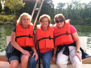 three caregiver friends riding boat on a retreat