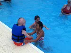 Child with Down Syndrome playing in pool with two friends
