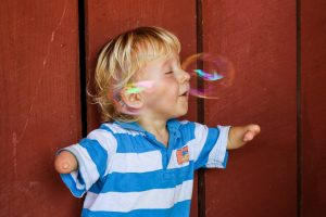 three year old boy blowing bubbles