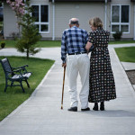 Woman walking down sidewalk with elderly man with cane