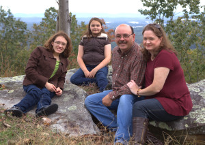 Mattheiss Family Photo, (L-r) Emily, Caroline, Jeff, Lisa sitting on stone with trees in background
